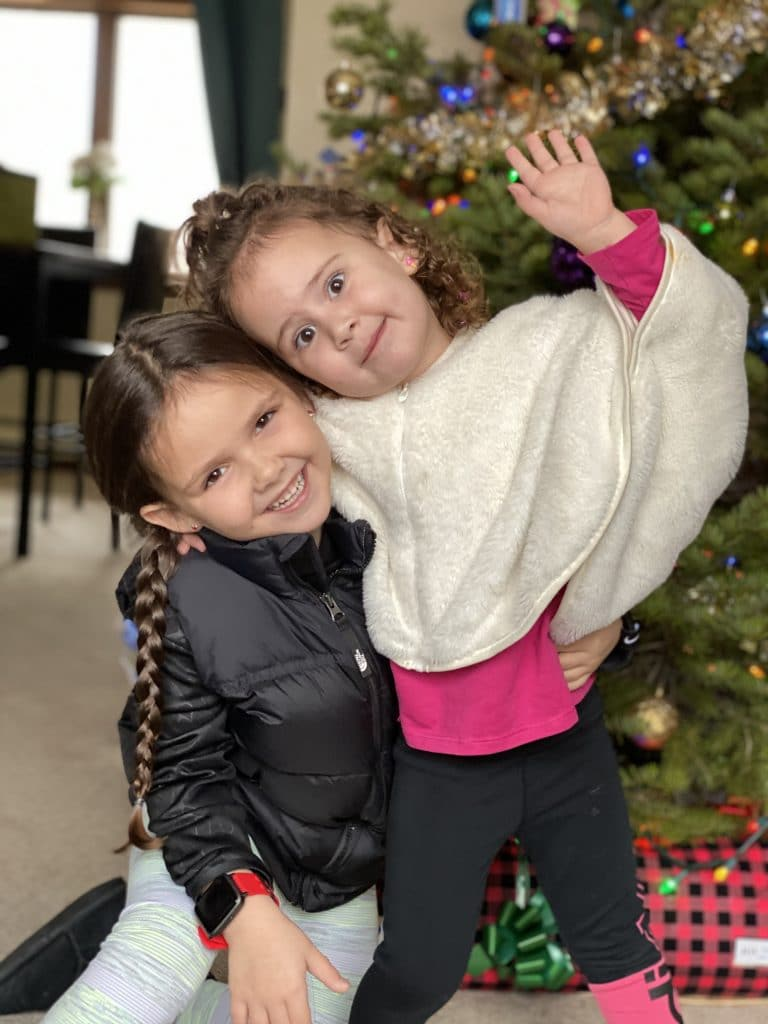Sisters standing in front of the Christmas tree